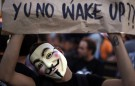 A demonstrator wearing a Guy Fawkes mask holds a banner during a protest at the Portuguese parliament as part of the United for Global Change movement in Lisbon